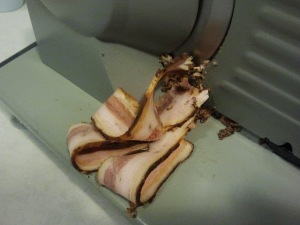 Bacon being sliced on a meat slicer