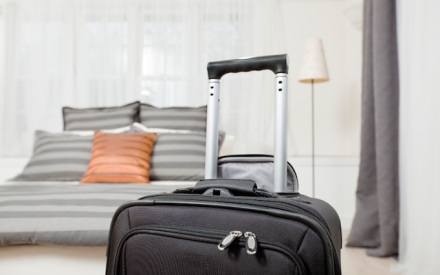 A suitcase in front of a bed in a hotel room