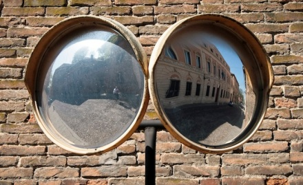 Two round street mirrors in front of a brick wall
